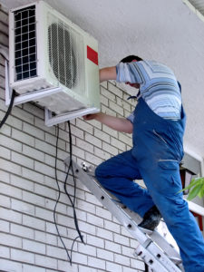 Canberra based Air Conditioning Installation technician looking at external unit